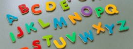 tabletop composition - colourful magnet letters form the abc / Alphabet on a grey metal background